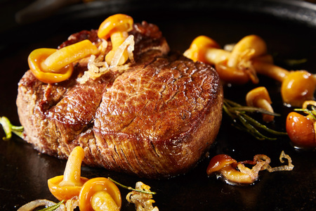 Gourmet grilled wild venison steak with mushrooms, herbs and onion in a close up low angle view suitable for menu advertising for a restaurant