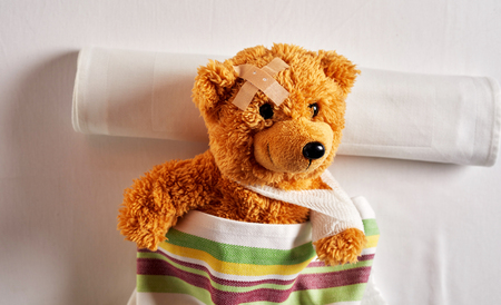 Little brown teddy bear lying in a hospital bed with a plaster on its head and bandaged arm in a sling after an accident viewed from above under a colorful blanket in a concept of paediatric medicine for kids Zdjęcie Seryjne