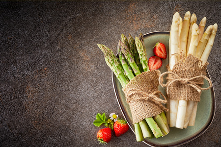 Bunches of fresh white and green asparagus tied with hessian and string on a plate with strawberries over a grey stone background with copyspace