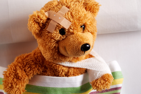Injured teddy bear with bandaged arm and head lying in bed after an accident in a closeup view in a concept of paediatric medicine for kids