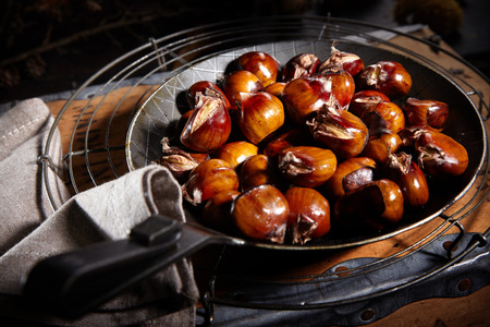 Pan of freshly roasted sweet chestnuts, or castanea, cooling on a wire rack on a rustic wood table on a shadowy background