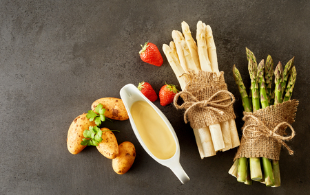 Assorted ingredients for a gourmet spring appetizer with two bundles of green and white asparagus spears, mayonnaise, strawberries and baby new potatoes on a grey background with copy space