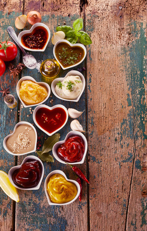 Overhead view of large assortment of sauces, dips and marinades in heart shaped bowls with scattered spices, herbs and condiments on a vertical rustic wood background