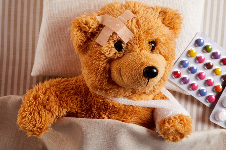 Little injured teddy bear lying sick in bed with a plaster on his forehead and bandaged arm in a sling alongside a blister pack of colorful pills in a concept of paediatric medicine for kids Banque d'images - 121548118
