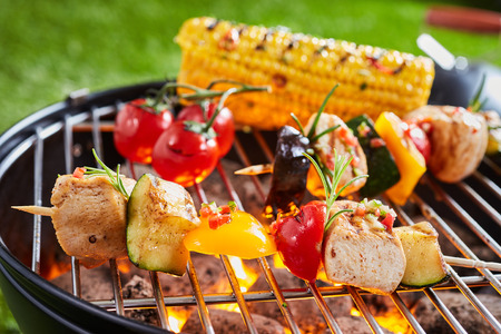 Vegetarian or vegan kebabs with tofu on the barbecue grilling over a hot fire outdoors with tomatoes and corn on the cob Stok Fotoğraf