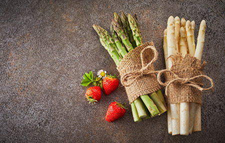Two bundles of fresh white and green asparagus spears lying on a textured grey background with copy space and three ripe strawberries