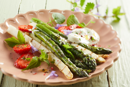 Grilled white and green asparagus spears with herbs, mayonnaise and sliced ripe red strawberries on a pink scalloped plate