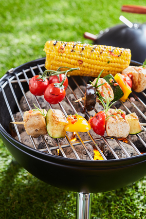 Grilling vegetables and meat kebabs on grid barbecue grill, viewed in close-up on green grass lawn