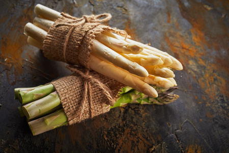 Close up on bunches of fresh white and green asparagus tied with rustic hessian an string on rusty metal