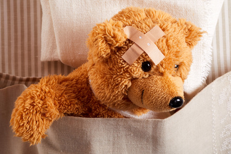 Cute little teddy bear with head trauma wearing a plaster on his forehead resting in bed in a close up on its face in a concept of paediatric medicine for kids
