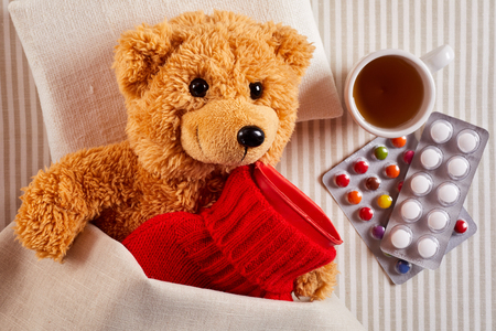 Sick little teddy bear lying in bed with a hot water bottle in a bright red knitted cover alongside a beverage in a cup and packs of pills and tablets in a concept of paediatric medicine for kids Banco de Imagens