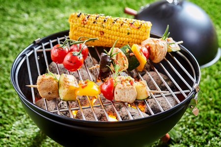 Vegetables and tofu kebab grilling on grid grille with fresh corn, viewed in close-up against green lawn grass in background