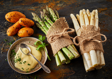 Fresh raw asparagus spears tied in bundles with mayonnaise in a side bowl and new baby potatoes on a rustic metal background viewed from above