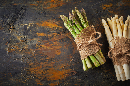 Fresh green and white spring asparagus tied in bundles with string and hessian over a rusty metal background with copy space 版權商用圖片