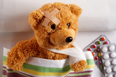 Injured teddy bear with arm in a sling and plaster on its head lying in bed alongside blister packs of tablets and pills, in a concept of paediatric medicine for kids Banque d'images - 121548138