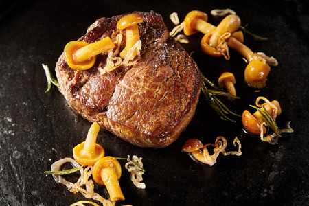 Thick juicy marinated grilled venison steak with forest mushrooms and onion in a black pan in close up view high angle