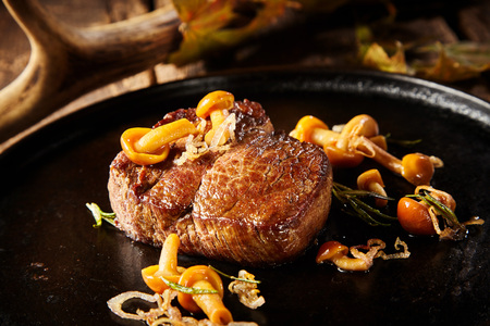 Thick portion of grilled wild venison deer steak with fried fall mushrooms and onions served in a metal pan in a close up view suitable for a menu Stock Photo