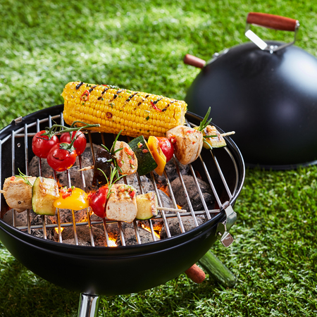Halloumi or tofu vegetarian kebabs grilling on an outdoor portable BBQ with corn on the cob on a green lawn in a concept of healthy outdoors summer lifestyle and vegan or vegetarian cuisine