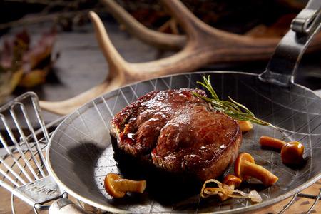 Bistec de venado salvaje a la parrilla, espeso y jugoso, servido en una sartén con setas del bosque y romero con un telón de fondo de cornamentas de ciervo Foto de archivo