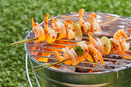 Gourmet spicy prawn kebabs on skewers grilling on a BBQ fire on a portable novelty bucket barbecue outdoors on green grass
