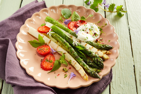 Grilled tender fresh green and white asparagus shoots with coriander, mayonnaise and strawberries served on a pink plate in a high angle view for menu advertising