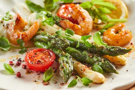 Antipasto gourmet di gamberi freschi e asparagi verdi e bianchi conditi con spezie e guarniti con erbe aromatiche in una vista ravvicinata ritagliata su un tardi