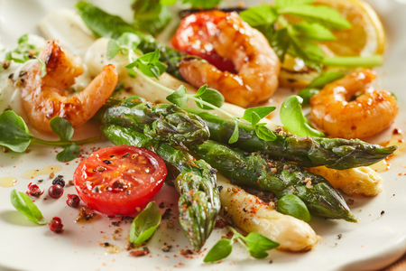 Gourmet fresh prawn and green and white asparagus appetizer seasoned with spices and garnished with herbs in a close up cropped view on a late