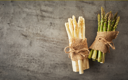 Two bunches of fresh white and green spring asparagus tips tied with string and burlap over a textured grey background with copy space