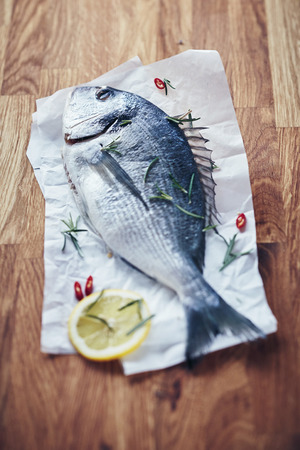 Whole fresh raw fish with chili and lemon facing away from the camera on crumpled white paper on a wooden table in a low angle shallow dof view