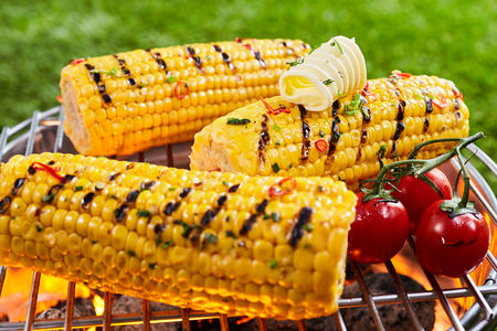 Delicious grilled corn on the grille with cherry tomatoes and a curl of butter, being prepared outdoors