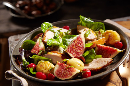 Wild salad with roasted sweet chestnuts, pheasant and ripe juicy figs served with basil, baby spinach and berries as a gourmet accompaniment to dinner