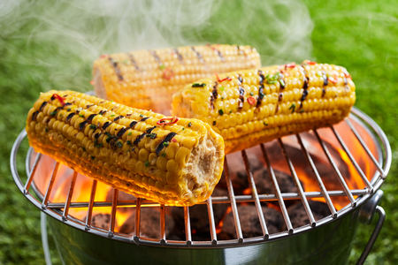 Grilling fresh corn on hot grid grill outdoors during picnic on green lawn. Close-up view with smoke