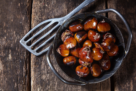 Old cast iron dish full of roasted chestnuts with a spatula alongside on an old rustic wood table, overhead view conceptual of autumn street food Stockfoto