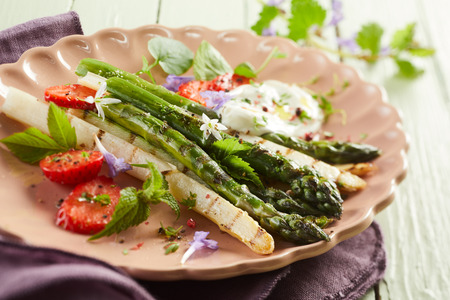 grilled tender fresh asparagus shoots with strawberries and mayonnaise garnished with assorted chopped herbs and served on a pink plate