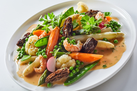 Gourmet appetizer with morel mushrooms, fresh white asparagus spears and shrimp served with mangetout peas, petit pois, cauliflower and carrots