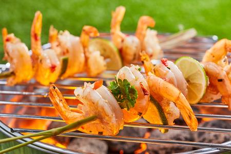 为了健康的户外生活,春天在公园或花园的户外烧烤上用烤肉串烤香辣虾尾