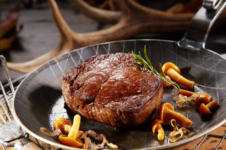 Marinated wild venison deer steak with mushrooms and rosemary served in a pan with a shed antler behind Stok Fotoğraf