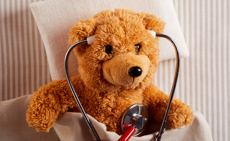 Cute plush teddy bear using a stethoscope to listen to its own heart as it lies ill in bed in a concept of paediatric medicine and cardiology for kids