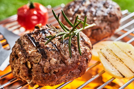 Grilled meat medallions and vegetables on hot metal barbecue grid with fresh greens on top. Outdoor picnic bbq concept