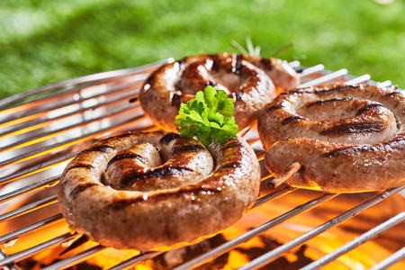 Coils of succulent beef sausage on a barbecue grilling over the hot coals outdoors in the garden or park on a summer picnic
