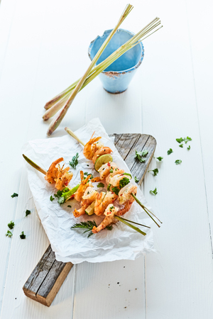 Gourmet grilled prawn tails seasoned with chilli spice and fresh herbs on bamboo skewers served on an old rustic wooden board on a white outdoor table Imagens