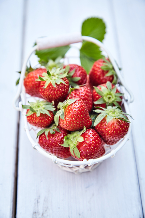 High-angle close-up view of a rustic basket full of fresh and nutritious strawberries on a wooden table outdoors with copy space