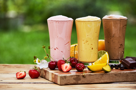 Three delicious fresh tropical fruit and chocolate milkshakes and smoothies served in tall glasses outdoors on a wooden board in the garden