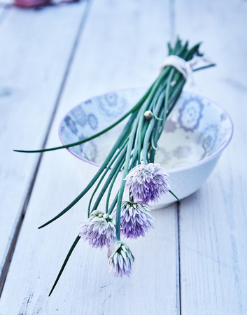 Bunch of purple onion flowers on ceramic bowl sitting on painted white wooden table, viewed in close-up Stock Photo