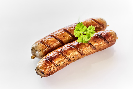 Close-up view of two grilled sausages on white background with a leaf of fresh green parsley