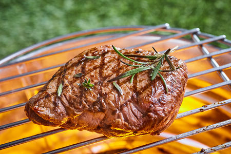 Thick juicy portion of beef fillet steak garnished with fresh rosemary on the BBQ grilling over the glowing hot coals in a close up view outdoors