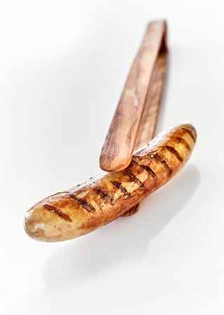 Single barbecued or grilled juicy pork sausage being presented with bamboo tongs over white with copy space for menu advertising