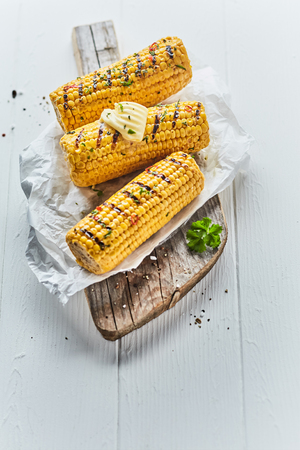 Three tasty grilled corn on the cob topped with farm butter served o crumpled paper on a wooden board outdoors at a summer picnic or barbecue Imagens
