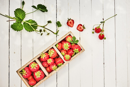 Wooden box of fresh whole ripe red strawberries on a white outdoor table at farmers market viewed from overhead with copy space and leaves