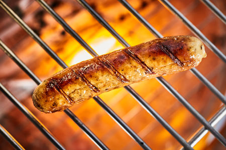 Grilling one delicious meat sausage on hot barbecue grill, viewed in full frame close-up from above